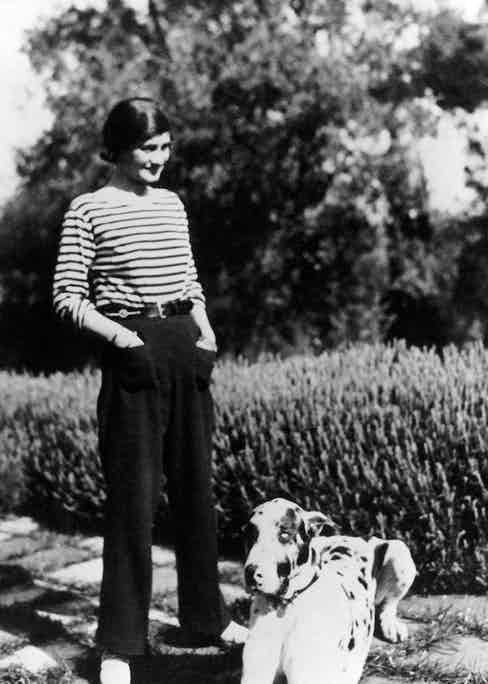 Coco Chanel at her home, Villa La Pausa in Roquebrune, in the French Riviera with her dog, Gigot, circa 1930. Photo by Alamy.