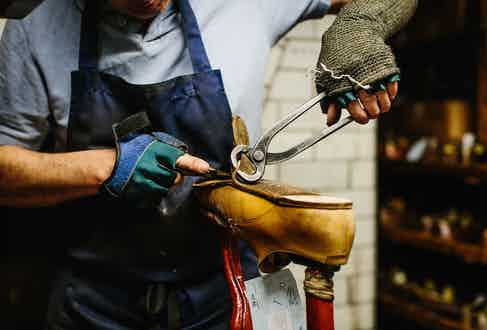 Removing a worn-out sole in the repair shop.