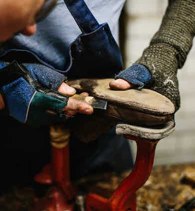 Cutting the sole stitch from an old pair of shoes in the repair room.
