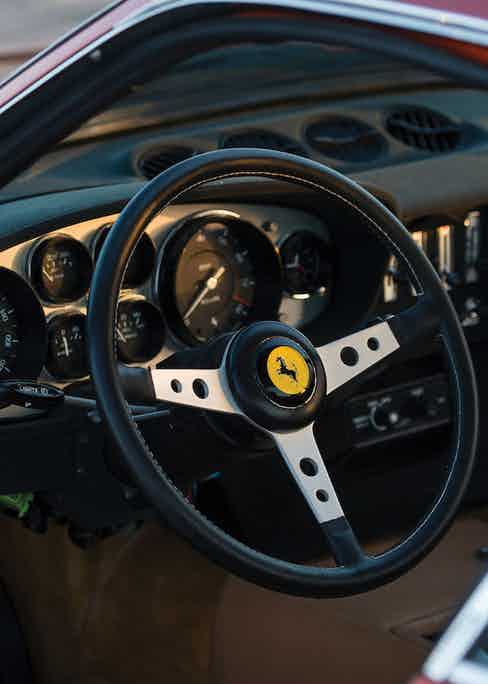 The simple dashboard features numerous circular dials and the large circumference Ferrari three-spoke steering wheel.