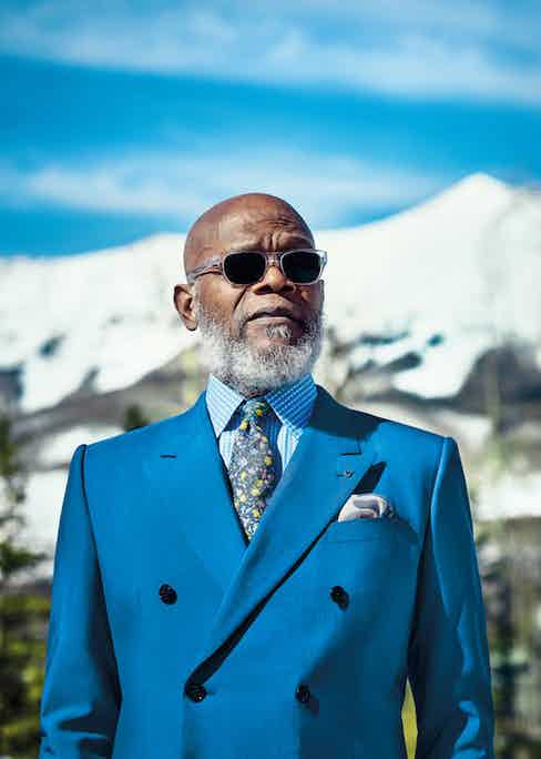 Samuel L Jackson wears Brandeis blue wool-silk double-breasted suit, Dolce & Gabanna; sky blue and white check cotton shirt and silk pocket-handkerchief, both Budd Shirtmakers; Blue and yellow flora silk print tie, Polo Ralph Lauren and vintage mother of pearl boutonniere, both property of The Rake; eyeframes, Barton Perreira, property of Samuel L Jackson in Issue 39 of The Rake. Art and fashion director: Sarah Ann Murray. Photography by Tomo Brejc.
