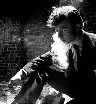 A Teddy boy enjoys a cigarette in the Elephant and Castle area, South London, 1955. Photo by Popperfoto/Getty Images.