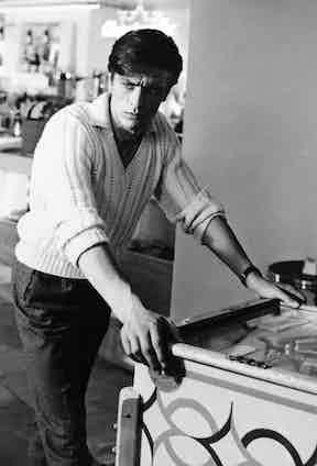 Alain Delon poses by a pinball machine, c. 1955. Photo by Alamy.