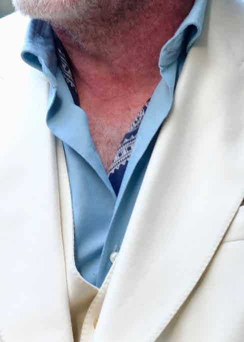 """The intriguing bandana that peeks out from underneath his Bagutta powder-blue shirt is a 1920s Elephant bandana. So often does he wear one - always with the trunks facing downwards - they're like """"a second skin""""."""