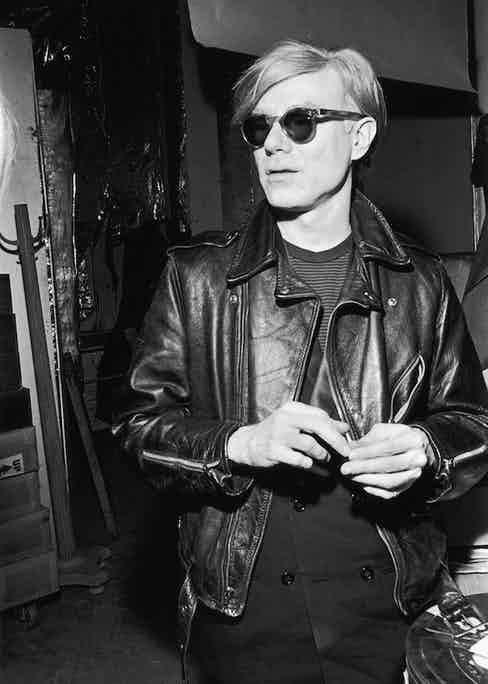 Artfully wearing a leather motorcycle jackets over a double-breasted blazer and striped t-shirt, circa 1970s.