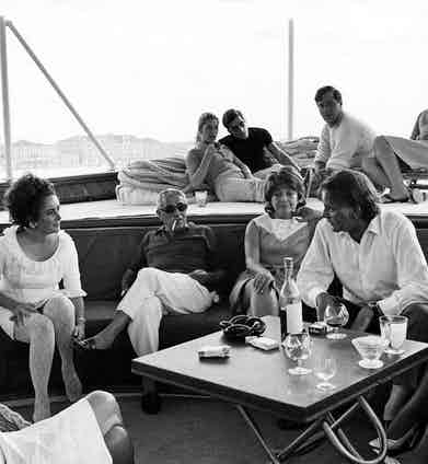 Elizabeth Taylor and Richard Burton sit with Aristotle Onassis aboard his yacht 'Christina O' in 1975. Photo by Harry Fox/REX/Shutterstock.