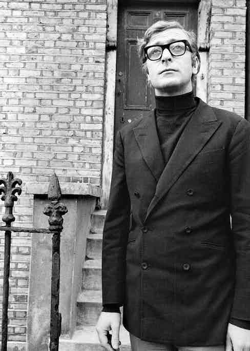 Caine visits his old neighbourhood in 1969 whilst wearing a mod-inspired, high-buttoning 6x2 double-breasted blazer and roll-neck combination.