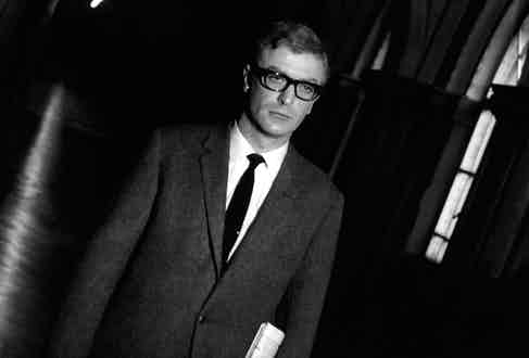 Caine in The Ipcress File in 1965, wearing a slightly looser cut suit than usual yet with his signature horn-rimmed glasses and somewhat vacant gaze.