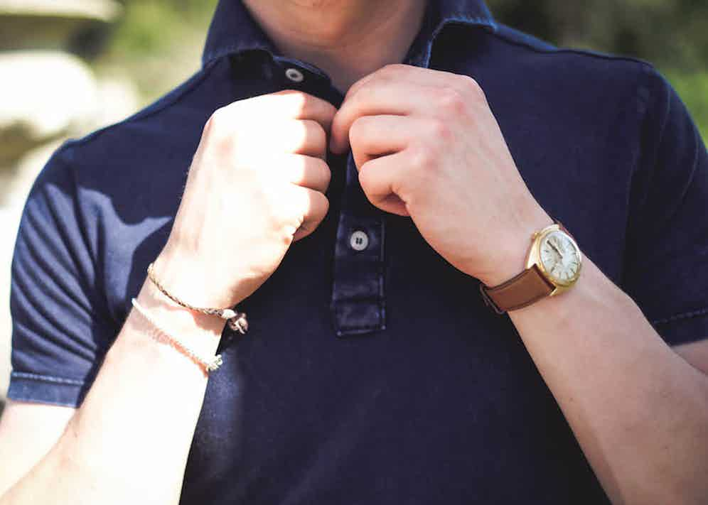 Navy short sleeve pique acid washed cotton polo shirt, Naked Clothing; beige manny pleated cotton trousers, Rubbinacci; watch, vintage Omega, property of The Rake.
