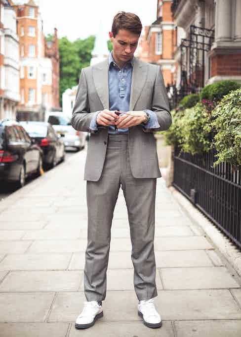 Dark blue long sleeve acid washed pique polo shirt, Naked Clothing; grey suit, Chester Barrie; white sneakers, Brunello Cucinelli; watch, Rolex property of The Rake.