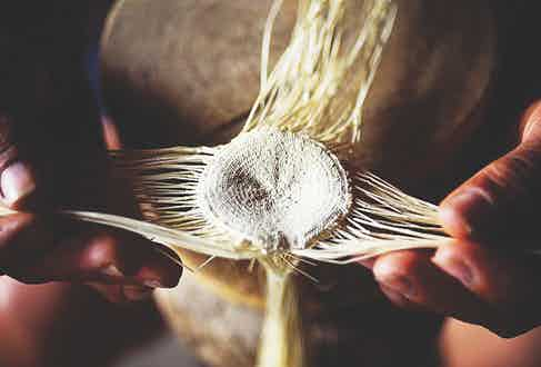 The weaving process begins with the creation of a small cross of four pairs of straws, interwoven to create the 'plantilla'.