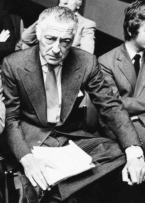 Agnelli wearing a signature grey flannel, peak-lapel suit with suede work boots, circa 1960s. Note his wristwatch, which is being worn on the outside of his shirt cuff.