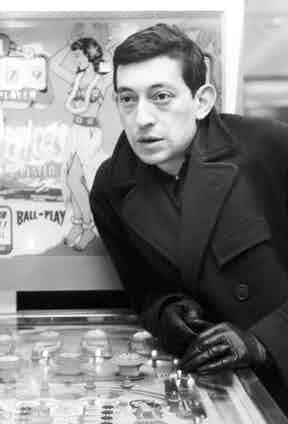 Looking minimalist and clean cut in one of his many fitted Paletots and black leather gloves, circa 1965.