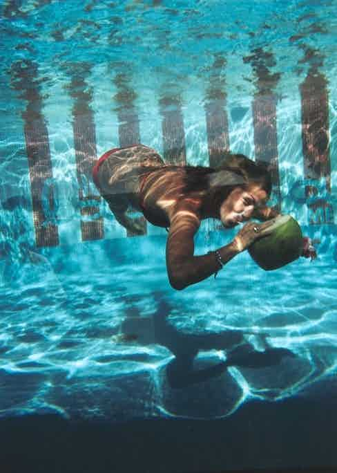 A woman drinking from a coconut underwater in the pool at Las Brisas Hotel in Acapulco, Mexico, February 1972. Photo by Slim Aarons.