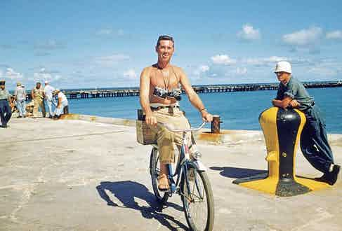 Slim Aarons riding a bicycle with his cameras around his neck, 1955.