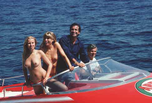 Actor George Hamilton takes off in a speedboat with friends Ruth Luthi and Mike Belami, during a stay in St Tropez, August 1977. Photo by Slim Aarons/Getty Images.