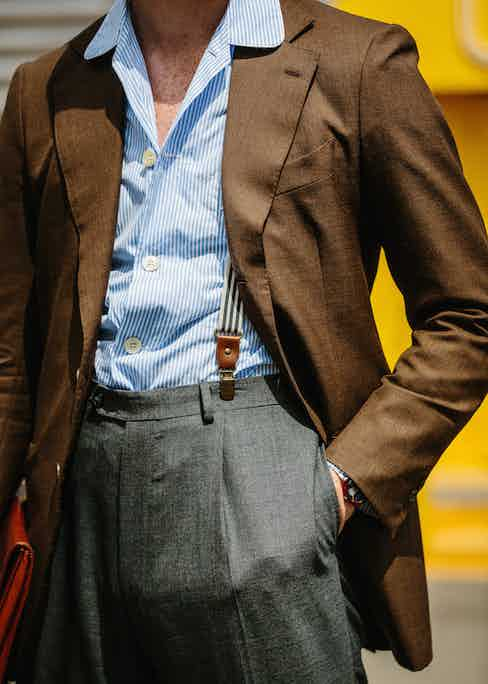 Clip-on braces worn with high-waisted, pleated trousers. Up top, the striped, camp collar shirt wears well over the brown blazer.
