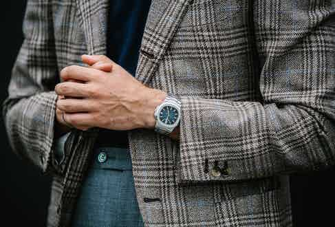 Up close with a Patek Philippe Nautilus, its blue dial complementing the blue overcheck on the jacket as well as the navy hue of the polo shirt.
