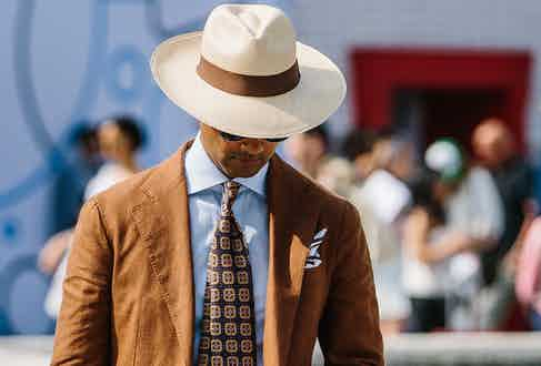 An elegant tobacco linen suit, paired with a printed silk tie and wide-brim Panama hat.