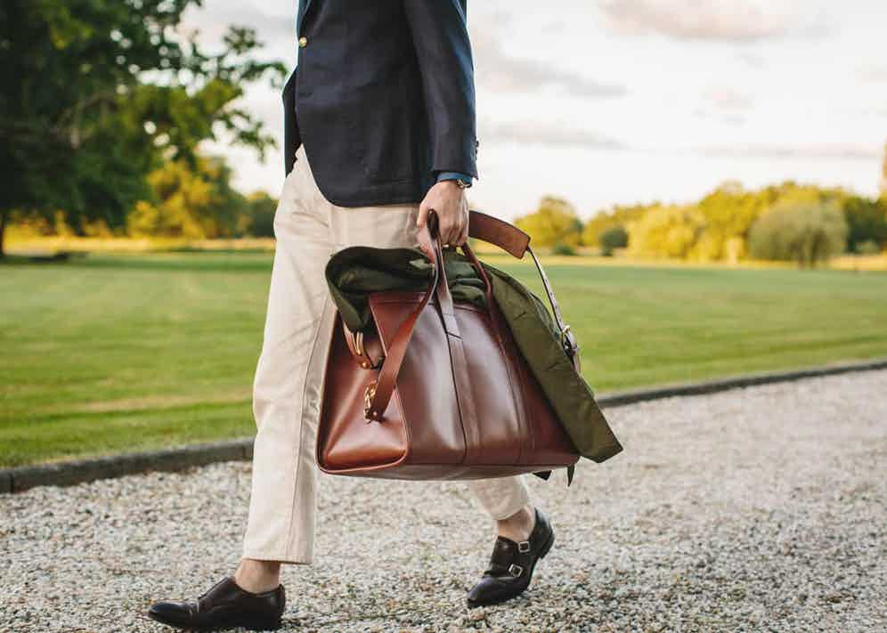 The Rake's Ben St George wearing a Sciamat blazer, Carmina cordovan monk straps and carrying a Grenfell Shooter jacket and a Frank Clegg signature leather travel duffle.