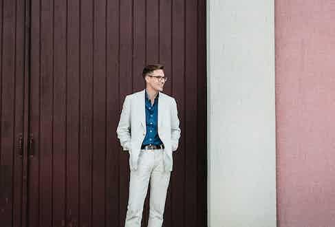 The Rake's Ben St George wears Huntsman's cream linen herringbone blazer and Drake's raw indigo-dyed denim cutaway collar shirt.
