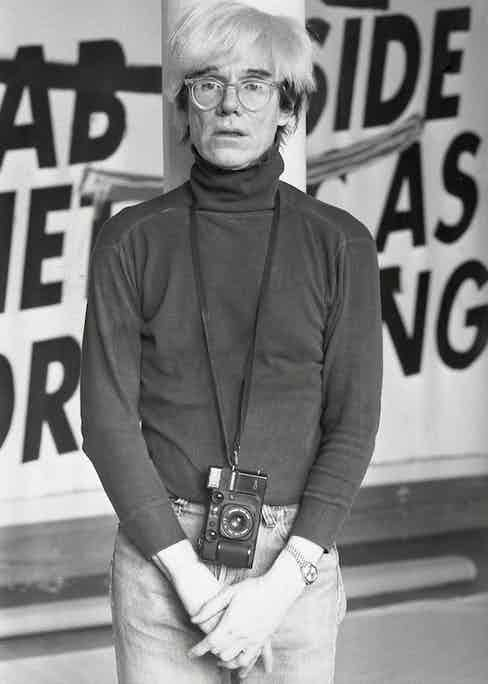 Warhol posing with his camera, trademark glasses and his ladies' Rolex Datejust wristwatch, 1984.