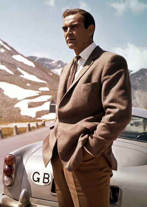 Sean Connery as James Bond, wearing a brown hacking jacket and standing next to his Aston Martin DB5 in the mountains of Switzerland, in the movie Goldfinger, 1964.