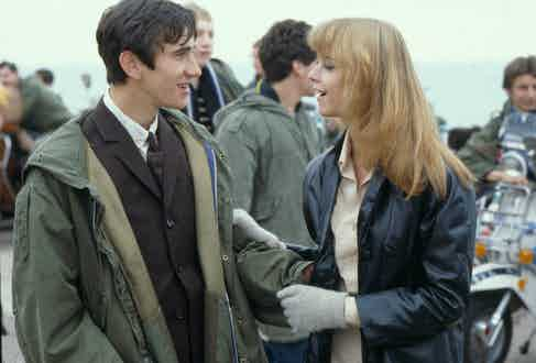 Phil Daniels alongside Leslie Ash in Quadrophenia, 1979. Phil's character, Jimmy Cooper, wears a brown, three-button suit in the modernist style, paired with an army-surplus parka over the top.