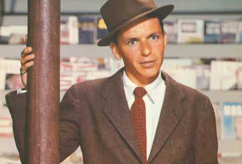 Frank Sinatra wearing a brown sack suit with a tilted fedora, circa 1950s.