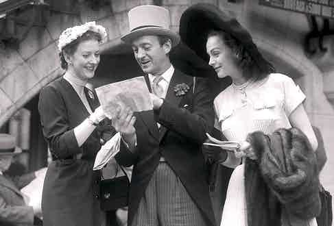 David Niven giving directions at the races with his wife, Hjordis on his right. Note his traditional charcoal striped trousers and voluptuous lapels.