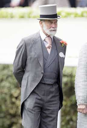 Prince Michael of Kent showcasing his trademark Windsor tie knot complete with complementary lapel flower.