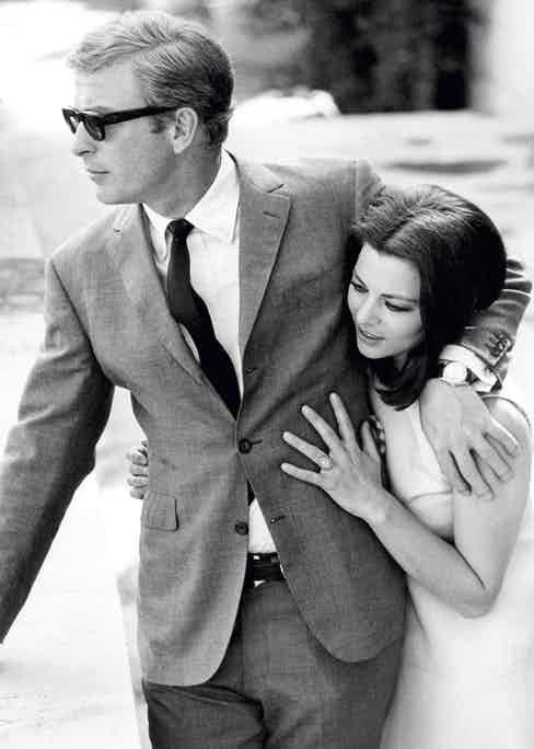 Michael Caine pictured with Giovanna Ralli in 1968. This classic Caine ensemble features a 'three-roll-two' suit jacket with slim notch lapels worn without a pocket square, for ultimate pared-back simplicity. Photo by Terry O'Neill/Getty Images