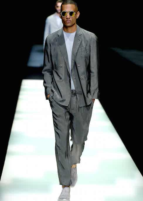 Giorgio Armani: A classic Armani look featuring an unstructured double-breasted suit crafted from a fluid silk-like fabric. Note the pleated, tapered trousers, which sit just above the trainers.