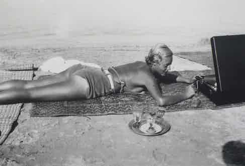 Chou Valton adjusts her record player at la Garoupe beach in 1932.