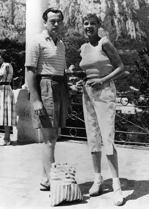 David Mountbatten, 3rd Marquess of Milford Haven wearing wide-legged, pleated shorts with Eva Bartok, 1953.