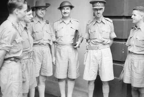 British soldiers stationed in Malaya, wearing high-waisted, Gurkha-style shorts as part of their lightweight Khaki Drill uniforms in 1942.