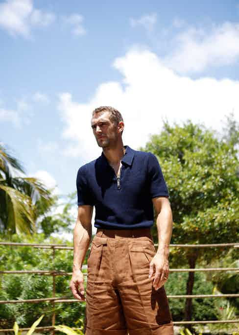 Navy knitted cotton short-sleeved polo shirt, Michael Kors; tobacco brown linen shorts, Chittleborough & Morgan. Photographed for The Rake by Kalle Gustafsson, styled by Jo Grzeszczuk on location at Maradiva Resort, Mauritius.