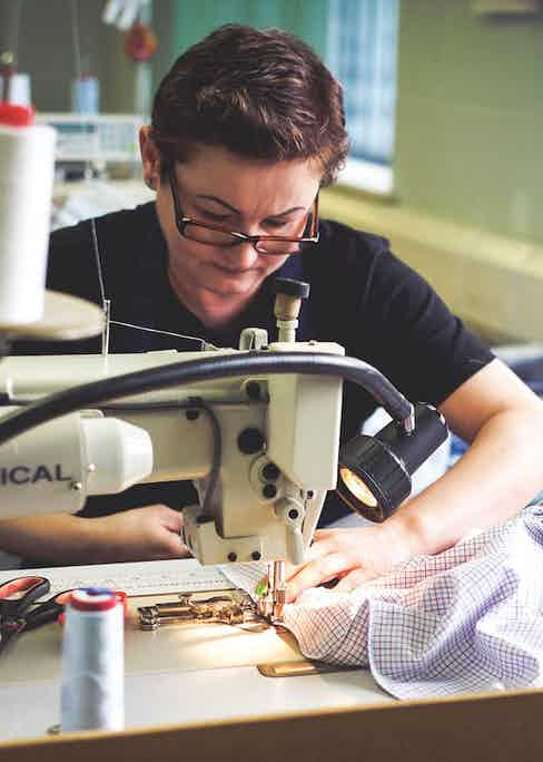Expert staff at work on the sewing machine in the Gloucester factory. Photo by Justin Hast.