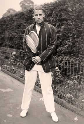 Bunny Austin in a striped sports jacket and whites, ready for a game in 1931. A year later he wore shorts at Forest Hills, and later went on to be the first player to wear shorts at Wimbledon.