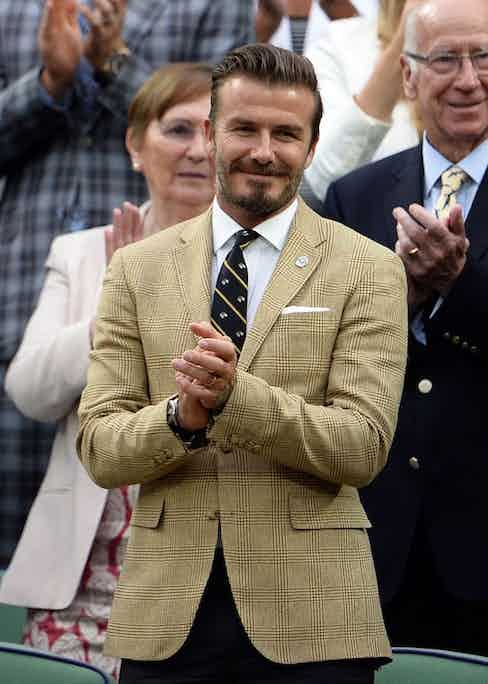 David Beckham masters tonal separates in the stands with a Prince of Wales check and brown trousers, 2014. Photo by Andrew Parsons/REX/Shutterstock.