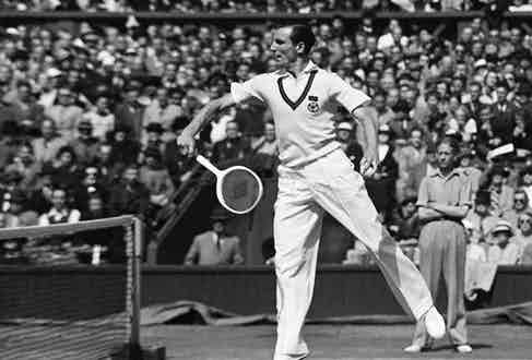 The stylish Fred Perry in a white sweater vest and with perfectly parted hair, playing at Wimbledon, 1936.