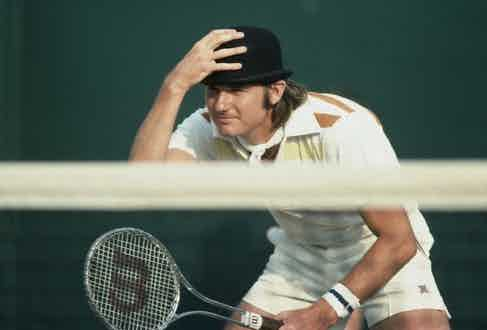 Jimmy Connors wearing a bowler hat during a Men's Doubles match at Wimbledon, 1976.