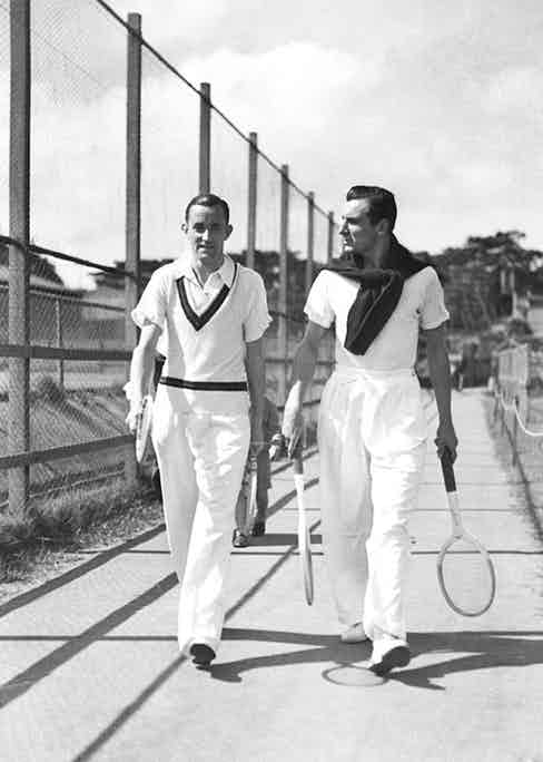 Pat Hughes and Fred Perry in Sydney, 1934. Perry (right) wears voluminous tailored white trousers with a jumper tied over his shoulders.