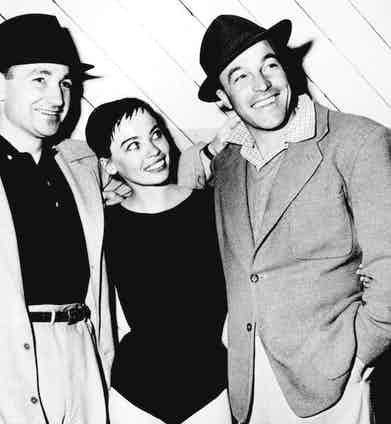 Gene Kelly with Leslie Caron and his brother Fred, 1951. Gene wears a classic trilby with a grosgrain trim, a single-breasted jacket with a full chest and generous lapels and a check shirt.