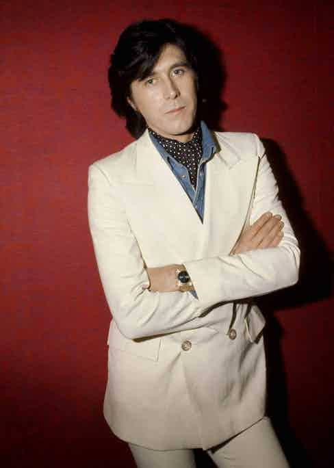 Bryan Ferry pairs a cravat with a white suit to add a hint of colour, 1973. Photo by Jorgen Angel/Redferns/Getty Images.
