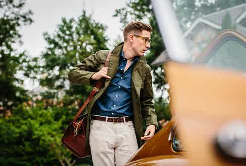 Grenfell's Green Cotton Shooter Jacket, Frank Clegg's Chestnut Signature Leather Travel Duffle and Drake's Raw Indigo Dyed Denim Cutaway Collar Shirt.