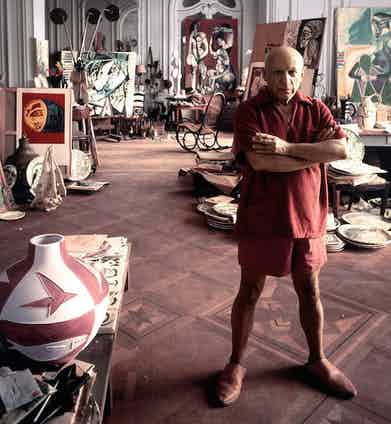 Pablo Picasso at his home studio in Cannes, 1956. He adopts a tonal red look, complete with a towelling polo shirt, wide leg shorts and leather espadrilles.