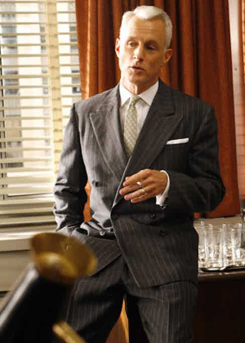 Roger Sterling makes a power play in a double-breasted charcoal suit with a wide pinstripe. The sloping shoulder and drape cut is true to the style of the time.
