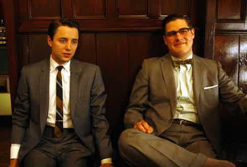 """Pete Campbell's perfectly executed parting and sober suits echoes Don Draper's style, while """"chronically uncool"""" Harry Crane's clip-on bow tie is a lesson in what not to wear."""