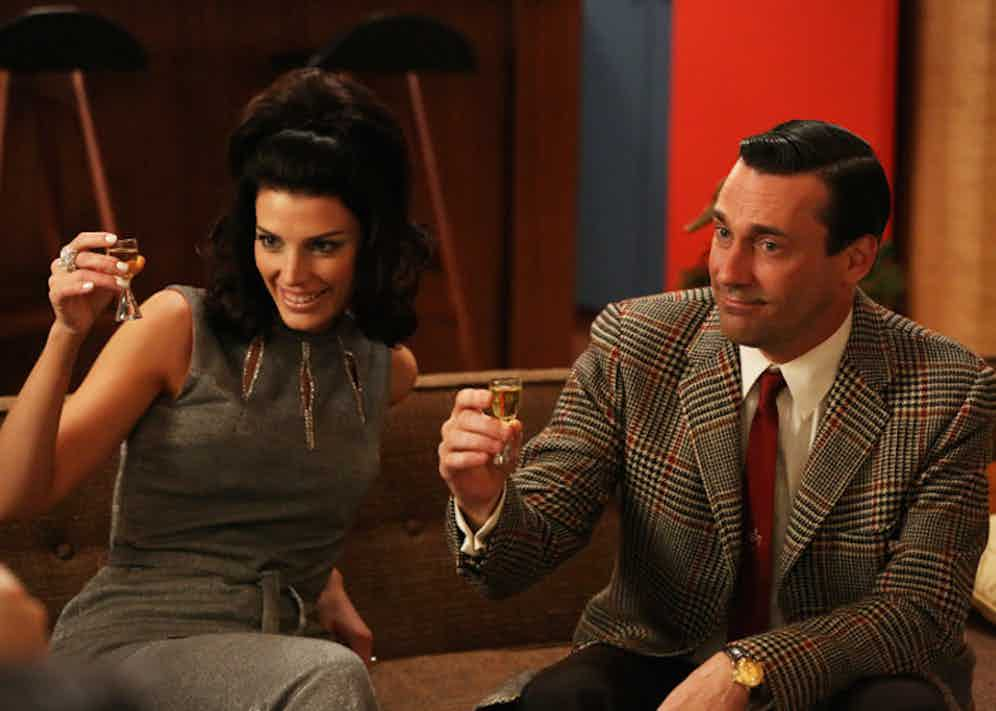 Don Draper toasts with his glamorous second wife Megan, wearing a bold Prince of Wales check jacket and monogrammed red tie. Throughout the series, he wears a series of vintage watches by Omega, Rolex and Jaeger-LeCoultre.